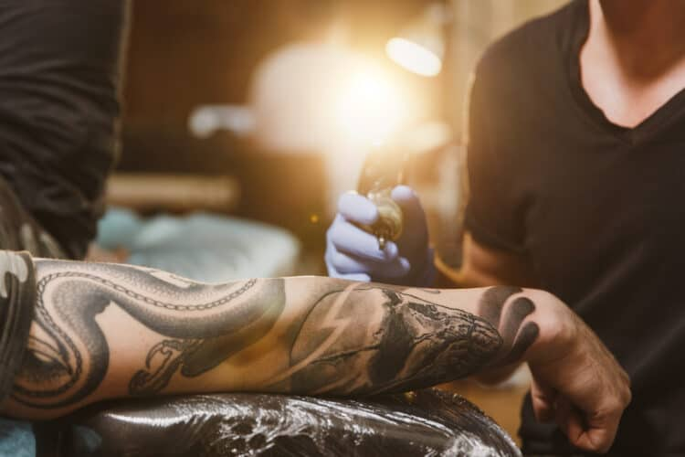 Close up of professional tattooer artist doing picture on hand of man by machine black ink from a jar. Tattoo art on body. Equipment for making tattoo art. Master makes tattooed in light studio