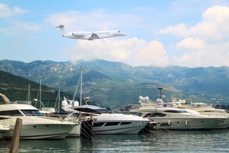Private jet business plane flies low over yachts and boats in gulf of  background of mountains with white clouds