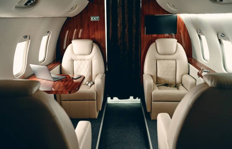 Cabin of luxury private jet. Empty aircraft with white leather chairs.