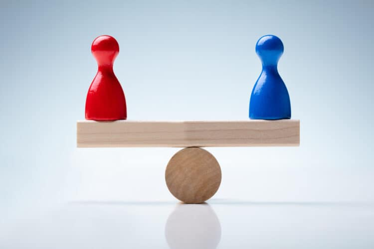 Red And Blue Pawn Figures On Wooden Seesaw Over Reflective Desk